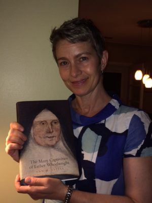 Dr. Ann Little holding a copy of her book