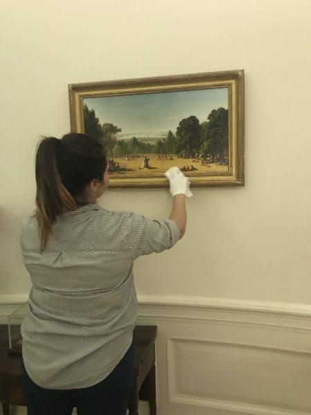 Kim Selinske cleans a painting