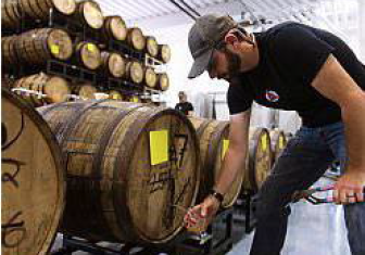 Travis Rupp fills a glass from a wooden keg