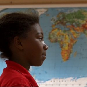 Student standing in front of a world map