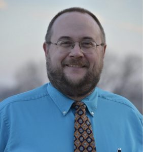 A professional photo of Dr. Derek Everett wearing a tie and blue shirt