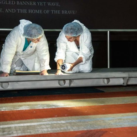 Two people examining an american flag